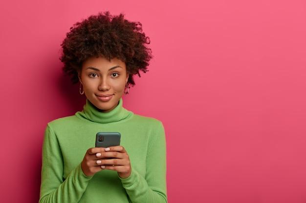 Goed uitziende vrouw met afro haartypes bericht op smartphone, bladert netwerk, kijkt vol vertrouwen naar de camera