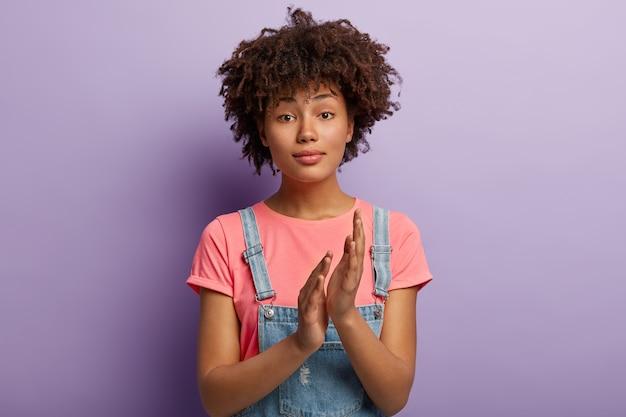 Goed uitziende vrouw met donkere huid wrijft over de handpalmen of applaudisseert, trots op mooie presentatie bij ontmoeting, heeft een nieuwsgierige blik, draagt vrijetijdskleding, waardeert iets, modellen over paarse muur.