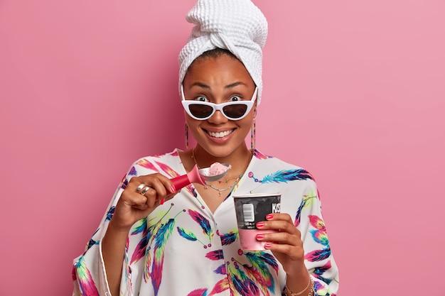 Goed uitziende vrouw met een donkere huid glimlacht en eet graag heerlijk ijs tijdens warme zomerdag draagt een zonnebril badjas en handdoek op het hoofd geïsoleerd over roze muur. huiselijk stijlconcept