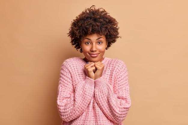 Goed uitziende vrouw met krullend haar houdt handen onder de kin kijkt direct naar de voorkant luistert iets aandachtig draagt casual gebreide trui geïsoleerd over bruine muur bewondert prachtig ding