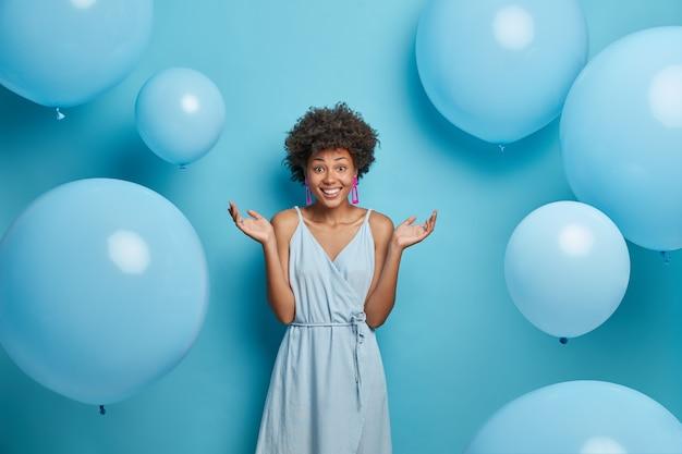 Goed uitziende vrouw met krullend haar spreidt handpalmen, glimlacht oprecht, geniet van zomerfeest, draagt blauwe jurk, staat tegen feestelijke luchtballonnen, heeft een gelukkig humeur, geïsoleerd. vrouwelijkheid, stijl, mode-concept