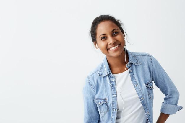 Goed uitziende vrouwelijke afro-amerikaan in blauw shirt met oprechte glimlach verheugt zich over haar succes op het werk met een goed humeur en toont haar positieve emoties. mensen, geluk, gezichtsuitdrukkingen en emoties.