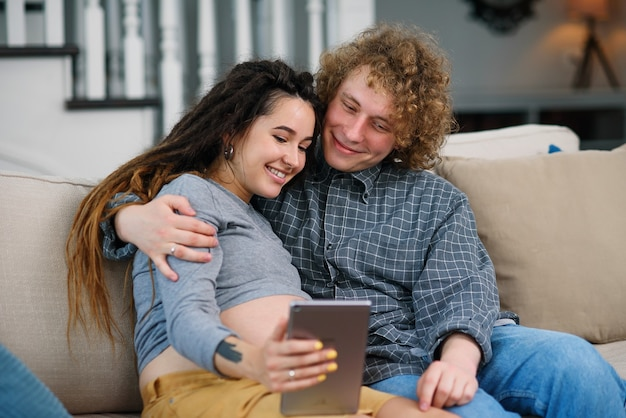 Goed uitziende zwangere paar ontspannen op de comfortabele bank thuis en tv-shows kijken