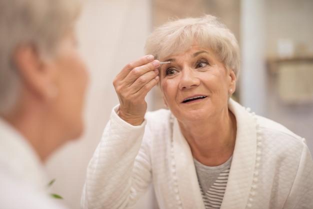 Goed verzorgde vrouw voor de spiegel