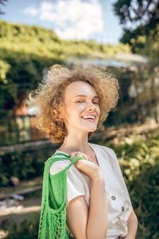Goed voelen. curly haired jonge vrouw een goed gevoel op een zonnige dag