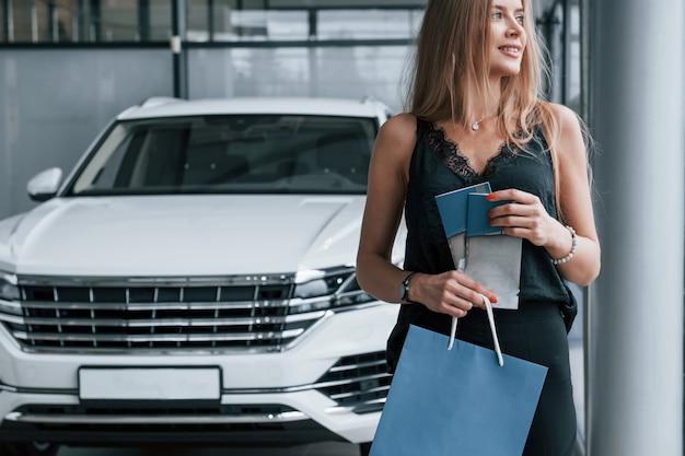 Goed voelen. meisje en moderne auto in de salon. overdag binnenshuis. een nieuw voertuig kopen