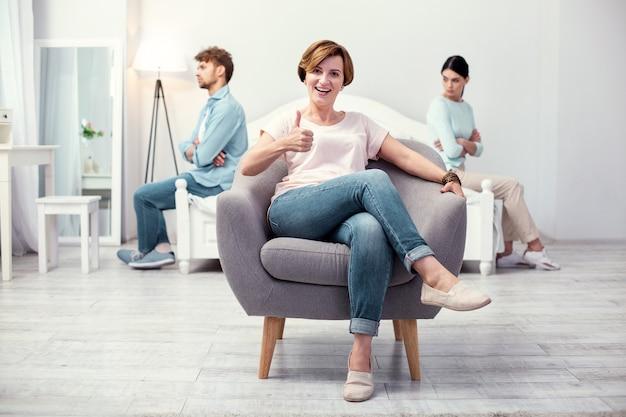 Goed werk. blije blije schoonmoeder zittend in de fauteuil terwijl ze duimen opdagen