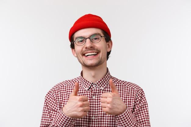 Goed werk, goed gedaan maat. ondersteunend schattig kaukasisch mannetje in bril en rode muts, laat thumbs-up tevreden zien, iets leuks goedkeuren of goedkeuren, tevreden glimlachen, staande witte muur