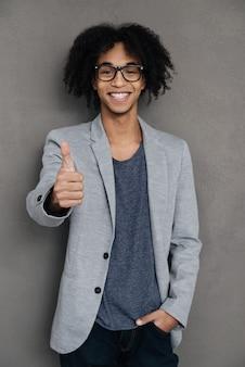 Goed werk! vrolijke jonge afrikaanse man die zijn duim opsteekt en glimlacht terwijl hij tegen een grijze achtergrond staat