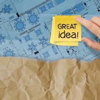 Goed werkwoord met notitie op bouwplaats en lay-outplan verfrommeld papier