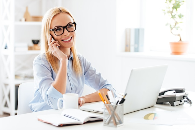 Goed zakelijk gesprek. vrolijke jonge mooie vrouw in glazen praten op mobiele telefoon en glimlachen terwijl ze op haar werkplek zit