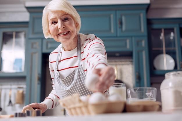 Goede bakker. de focus ligt op een aangename oudere dame die een ei uit een eierdoos haalt en naar de camera glimlacht terwijl ze deeg voor een taart maakt