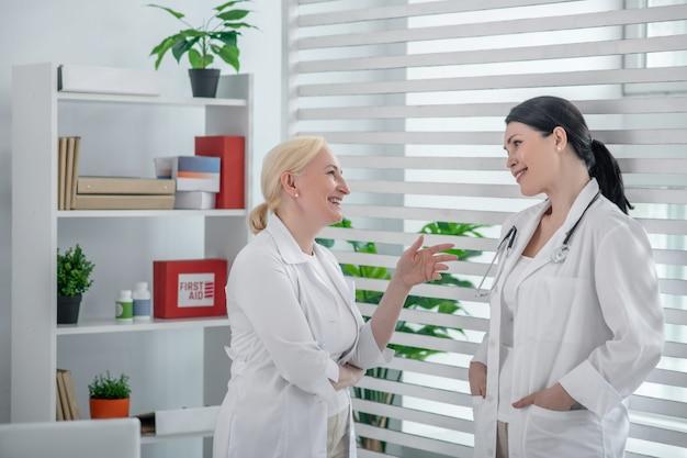 Goede dag. twee artsen in witte gewaden praten in het kantoor