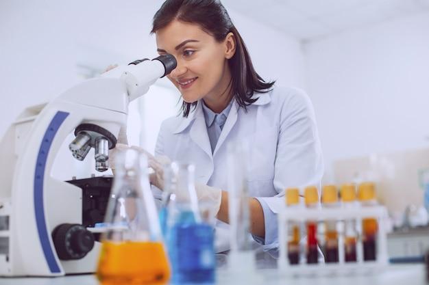 Goede dag. vrolijke professionele bioloog die een uniform draagt en in de microscoop kijkt