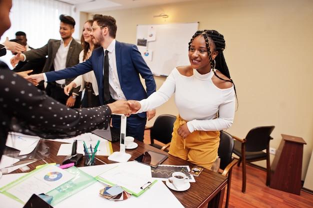 Goede deal. multiraciaal zakelijk team dat vergadering rond directiekamertafel behandelt en elkaar de hand schudt.