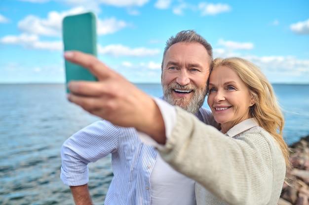 Goede foto. glimlachende mooie vrouw met smartphone in uitgestrekte hand en vrolijke bebaarde man die selfie neemt in de natuur in de buurt van zee