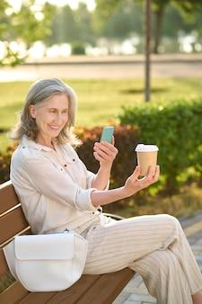 Goede foto. glimlachende volwassen vrouw in lichte broek en blouse die een foto neemt van een glas koffie op een smartphone die op een bankje zit