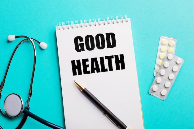 Goede gezondheid geschreven in een wit blocnote dichtbij een stethoscoop, pennen en pillen op lichtblauw