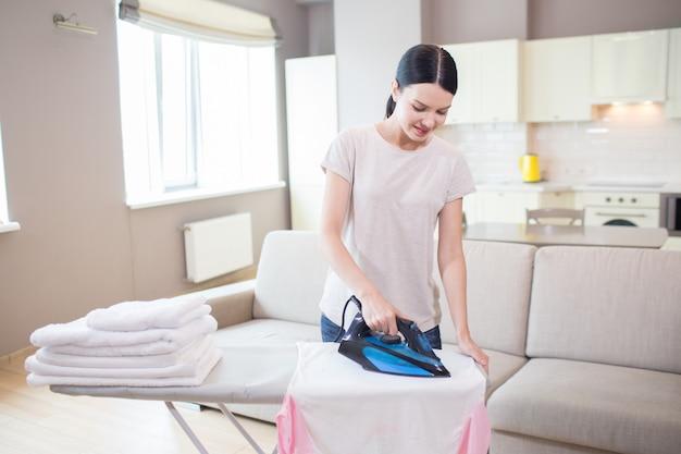 Goede huisbewaarder staat in studio-appartement en strijkt kleding. het ijzer is blauw. ze doet dat voorzichtig.