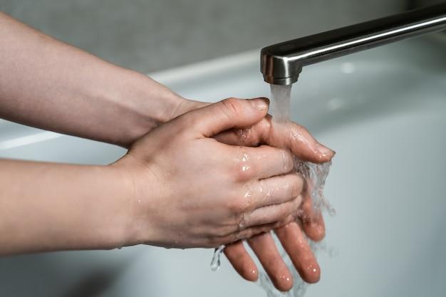 Goede hygiëne tijdens de pandemie van het coronavirus. vrouw wast handen in warm stromend water met zeep