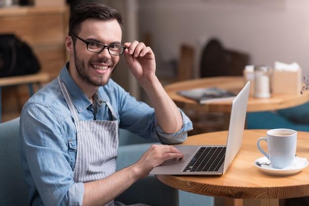 Goede ideeën. expressieve jonge bebaarde man glimlachend en zijn bril aan te raken tijdens het gebruik van laptop.