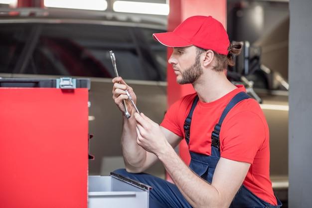 Goede keuze. jonge, bebaarde automonteur in rode pet en t-shirt met moersleutel zitten in de buurt van toolbox in werkplaats