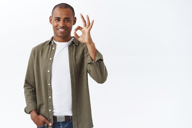 Goede kwaliteit, gegarandeerd dat je het leuk vindt. portret van zelfverzekerde afro-amerikaanse man toont oké, oké teken en glimlacht, knik goedkeurend