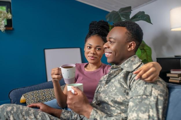 Goede momenten. donkere jonge militaire man in camouflage en mooie vrouw met kapsel die thuis koffie drinkt op de bank in een goed humeur