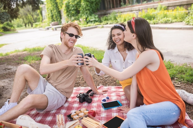 Goede momenten. drie gelukkige jonge vrienden met een drankje in handen zittend op deken communiceren op picknick in het park op fijne middag