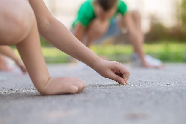 Goede momenten. kinderhand met kleurpotloden tekenen op asfalt in park op zomerdag, geen gezicht