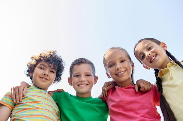Goede momenten. meisjes en jongens van basisschoolleeftijd gelukkig omarmen tegen lucht op mooie dag