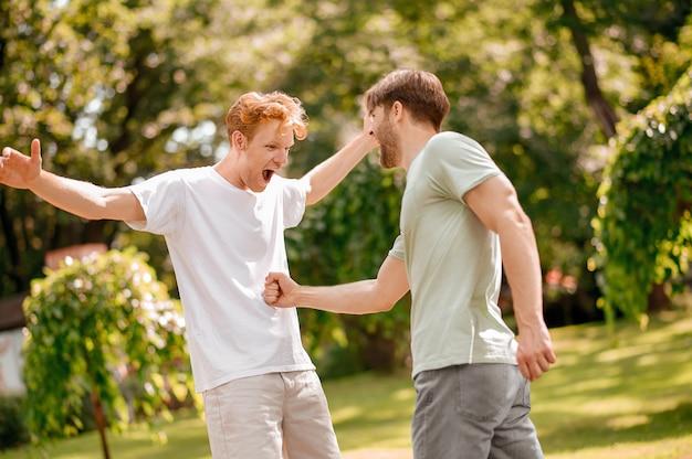 Goede momenten. twee gelukkige vrolijke jongens in vrijetijdskleding die plezier hebben en speels communiceren in de natuur op een warme zomerdag