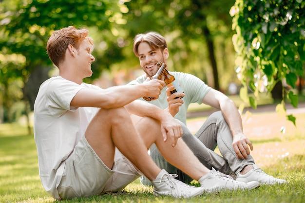 Goede momenten. twee gelukkige vrolijke vrienden in lichte vrijetijdskleding met flessen chatten op groen gazon op zonnige zomerdag