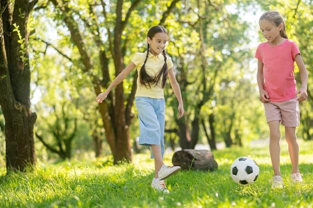 Goede momenten. twee vrolijke langharige vriendinnen van basisschoolleeftijd die op zomerdag voetballen op het gazon