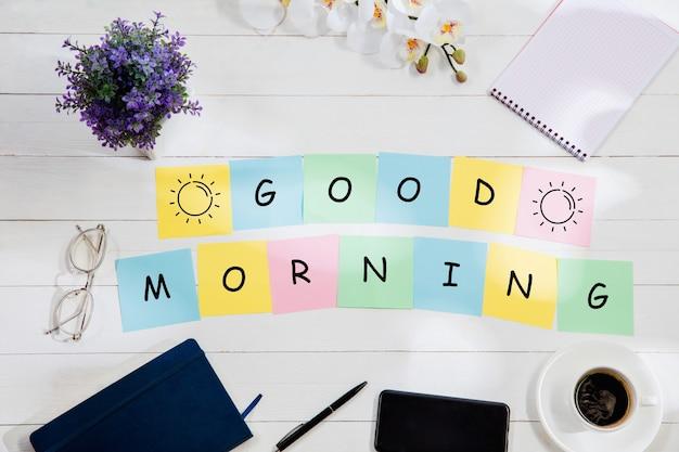 Goede morgen. bericht op kleurrijke notitieblaadjes op de achtergrond van een bureau.