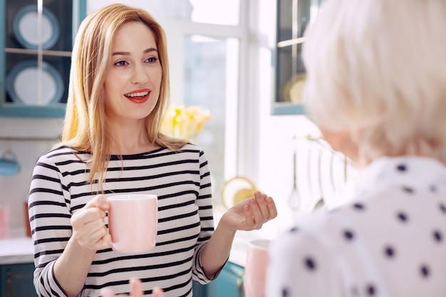Goede morgen. de focus ligt op een aangename jonge vrouw die met haar geliefde bejaarde moeder praat en naar haar glimlacht terwijl ze 's ochtends samen koffie drinkt in de keuken