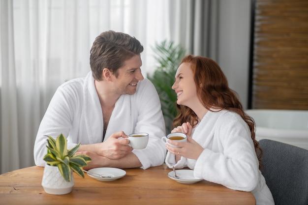 Goede morgen. een stel in witte badjassen dat koffie drinkt en zich gelukkig voelt