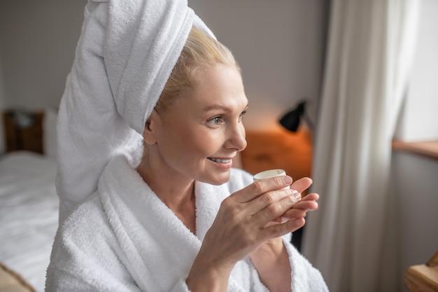 Goede morgen. een vrouw in het wit die naar het raam kijkt en haar ochtendthee drinkt