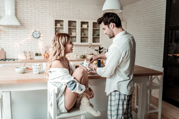 Goede morgen. glimlachende jonge langharige mooie vrouw die dikke sokken draagt die op de stoel zitten terwijl zij een ochtend met haar echtgenoot doorbrengt