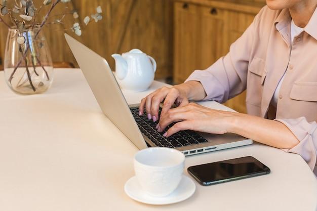 Goede morgen. vrolijk lachende bejaarde senior vrouw die in de keuken staat en haar laptop gebruikt terwijl ze rust na het ontbijt, freelancer die thuis werkt.