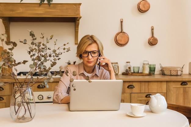 Goede morgen. vrolijk lachende bejaarde senior vrouw die in de keuken staat en haar laptop gebruikt terwijl ze rust na het ontbijt, thuis werkend. mobiele telefoon gebruiken.