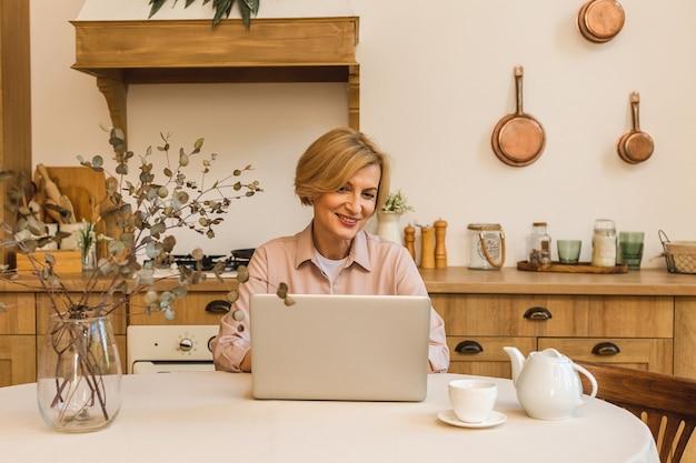 Goede morgen. vrolijk lachende bejaarde senior vrouw die in de keuken staat en haar laptop gebruikt terwijl ze rust na het ontbijt, thuis werkend.