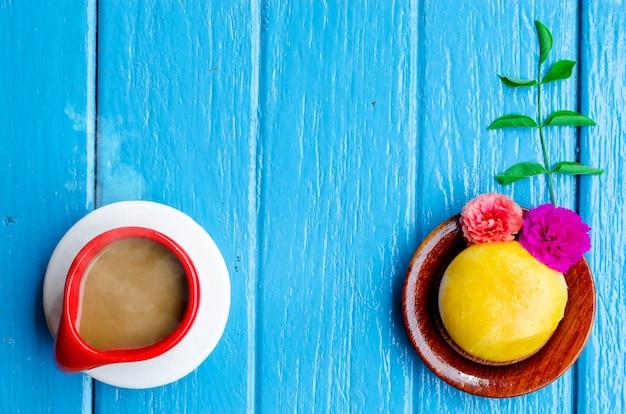 Goede morgen wereld. kopje koffie en gele taart op blauwe achtergrond