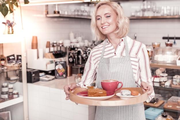 Goede service. blije, goed uitziende vrouw die lacht terwijl ze het ontbijt serveert aan de caféklanten