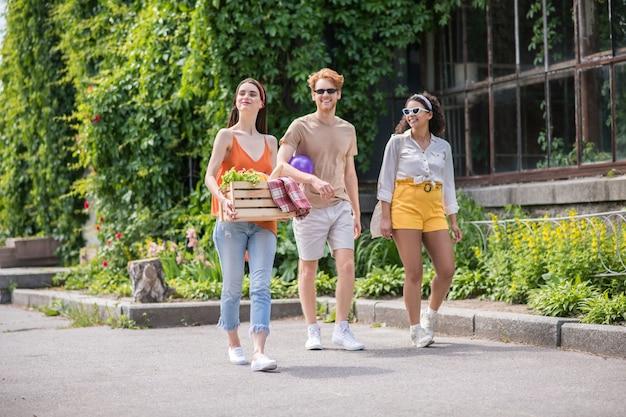 Goede tijd. gelukkige jonge lachende vrienden wandelen op picknick met geschenken en bal in groen park op warme dag