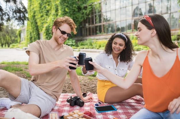 Goede tijd. groep optimistische vriendelijke jonge mensen die op een warme dag in het park onder de boom op de deken zitten met een drankje