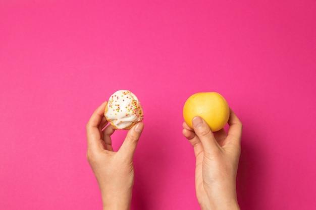 Goede voeding. vrouwelijke handen die een cake houden en groene band meten. dieet. slimming man.
