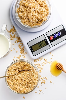 Goede voedingsmenu voor ontbijt met havermoutpap op digitale keukenweegschaal, melk en honing