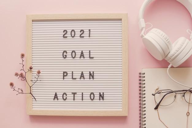 Goede voornemens voor het nieuwe jaar. doelplan en actie op letterbord met notitieblok en koptelefoon