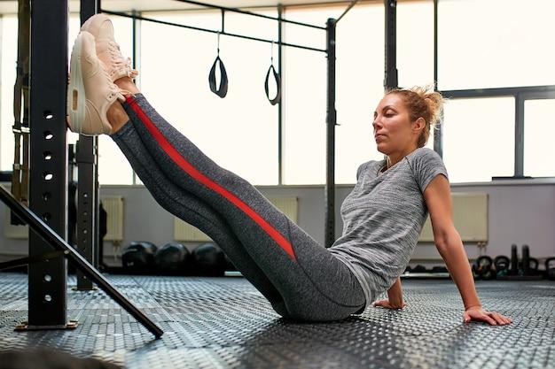 Goede vooruitgang. jonge mooie vrouw in sportkleding die het uitrekken zich voor venster doen bij gymnastiek